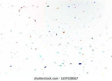 Thousands of confetti fired on air during a festival. Image ideal for backgrounds. Red are the confetti in the picture. White background. Smoke and shades