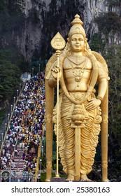 Thousands of Hindu Tamil Indians climbing steps to Batu Caves alongside statue of Lord Murugan in Kuala Lumpur, Malaysia for Thaipusam