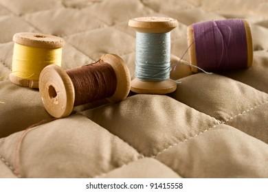 Thread bobbins on a beige fabric