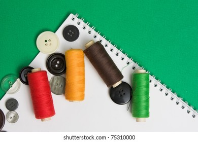 thread with a needle and buttons on the background of the notebook