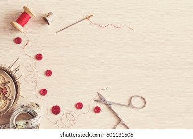 Thread, needle, scissors and buttons  - basic accessories starting sewing. Sewing works. Handmade.