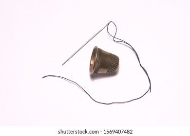 thread with a needle and a thimble on a white background