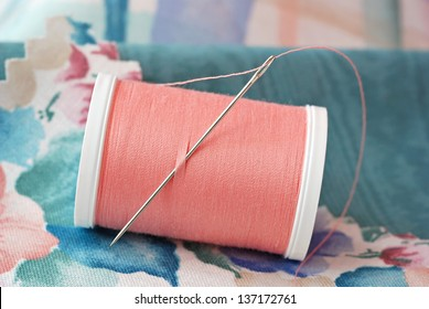Threaded needle in spool of peach colored polyester thread with swatches of fabric.  Macro with shallow dof.  Selective focus on needle.