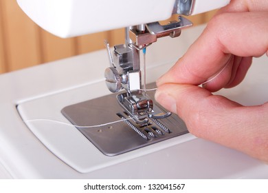 Threading a sewing machine hands showing
