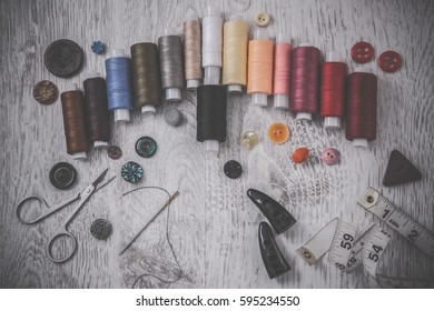 Threads, needle, scissors and buttons  - basic accessories starting sewing. Sewing works. Handmade.