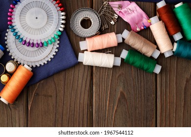 Threads and sewing accessories on brown wooden table