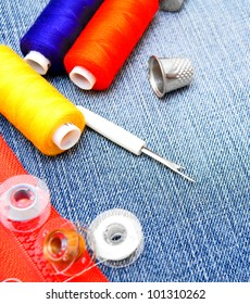 Threads, thimbles, zipper lock on a fabric.
