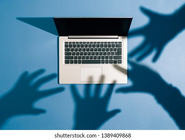 Threatening hands attacking a laptop and stealing information: cyber crime, hackers and malware concept