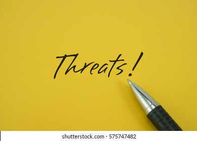 Threats! note with pen on yellow background