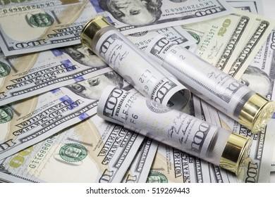 Three 12 caliber shotgun cartridges loaded with american 100 dollar bills on dollar bills background
