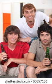 three 18 years old boys drinking beer at home