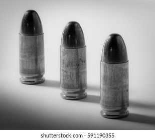 Three 9mm black & white bullets lined up in a row.