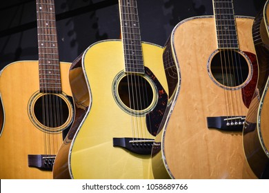 Three acoustic guitars hanging in a row - generic