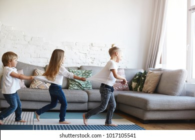 Three active barefooted Caucasian kids wearing similar clothes celebrating funny birthday party in living room, dancing, standing in conga line one after another, playing indoor games, feeling happy