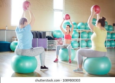 Three active girls with red balls in raised hands sitting on fitballs and exercising in gym