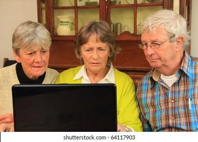 Three active senior citizens surfing the internet.