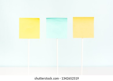 Three adhesive paper notes for text on stick. Empty board plank holder.