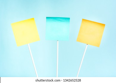 Three adhesive yellow, blue and orange paper notes on stick for text and blue background. Empty board plank holder.