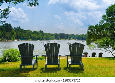 Three Adirondack chairs sit on a green grass facing a lake beach during a sunny summer day in Muskoka, Ontario Canada. People and boats are present in the water.