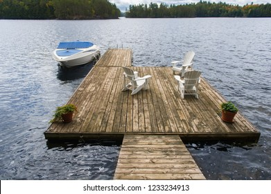 Three Adirondack chairs sitting on a wooden dock facing a calm lake in autumn. A motorboat is tied to the dock.