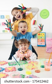 Three adorable kids with hands covered in paint