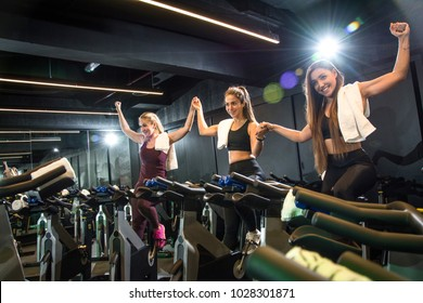 Three adorable pretty fitness girls holding hands together and celebrating progress in the gym.