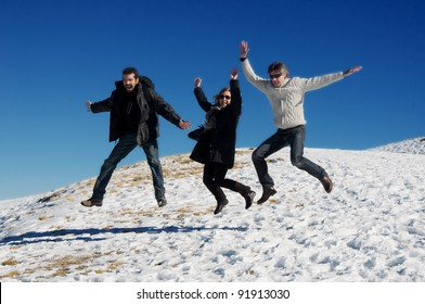 Three adult friends jumping in the snow