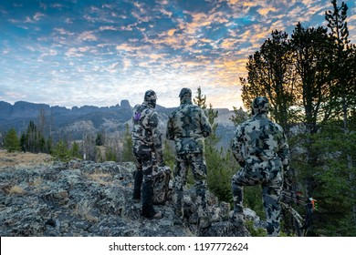 Three adult male hunter friends, unrecognizable,  stand on a mountain ridge looking for elk to hunt during bow archery season. Wearing camouflage