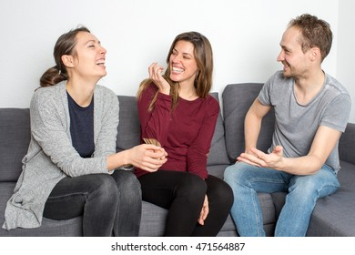 Three adult persons sitting laughing in living room