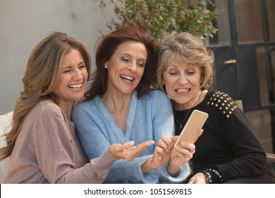 Three adult and senior women having fun with mobile phone