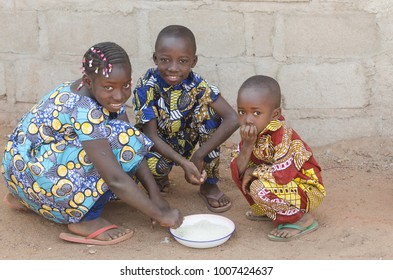 Three African Children Sitting Outdoors Eating Rice in Africa