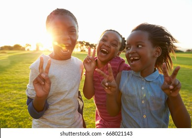 Three African elementary schoolgirls making peace signs