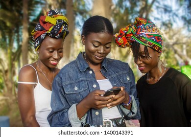 Three African Friends Smile While Reading A Message on a phone