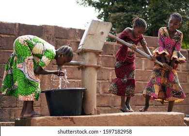 Three African Girls Filling Up Water Buckets At A Public Borhole Pump