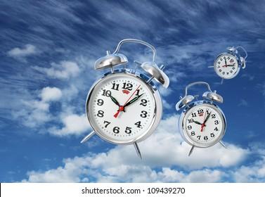 Three alarm clocks flying on blue sky, time flies concept