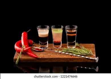 Three alcohol shooter layered cocktails on a wooden board served with barman spoon and chili pepper isolated at black background.