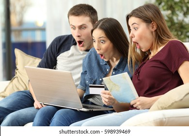 Three amazed friends finding trip offers on line with a laptop sitting on a couch in the living room in a house interior