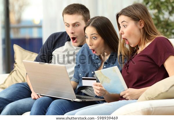 Drei verblüffte Freunde finden online mit einem Laptop auf einer Couch im Wohnzimmer in einem Wohnhaus-Interieur