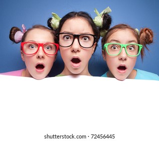 Three amazed teens with blank presentation board