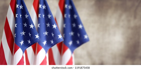Three American flags in front of blurred brown background