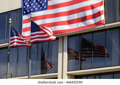 Three american flags with large glass windows in the background