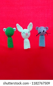 three amigurumi crochet finger puppets. frog, rabbit and mouse. isolated on red background.