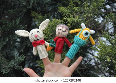 Three amigurumi finger puppets in front of green background