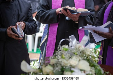 Three Anglican priests attending a funeral, next to the grave