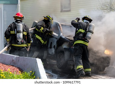 Three anonymous firemen with a burning car. One fireman sprays water through a window, another is prying the hood open. Badges and branding removed from car and fire equipment.