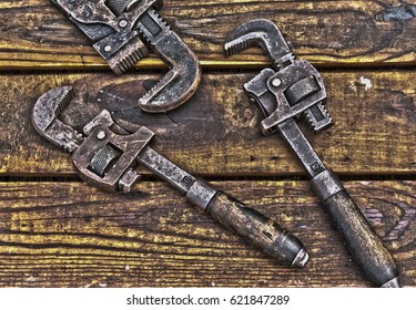 Three antique wrenches on rough wooden background