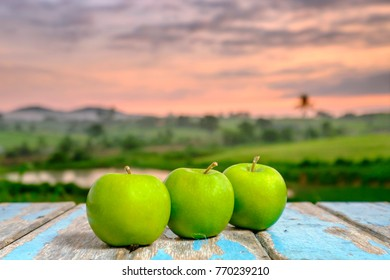 Three apples on wooden table in the sunlight with  a blurred nature  background.