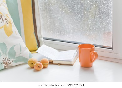 Three apricots on windowsill at the window with raindrops next to the book, pillow and cup on a rainy day. Set for a cozy summer reading.