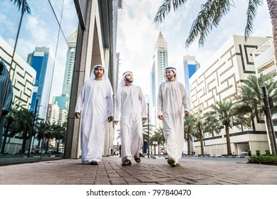 Three arabic men bonding outdoors - Businesspeople walking and talking in Dubai