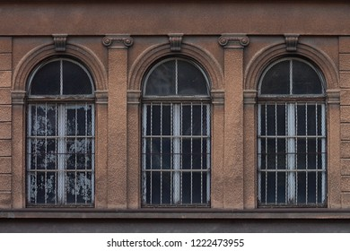Three arched windows on an old ornate facade
